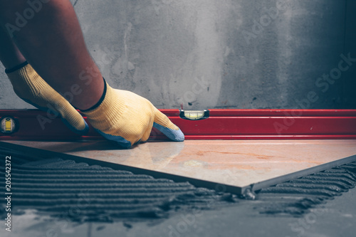 Obraz Working tiles lay a large tile on the floor - fototapety do salonu