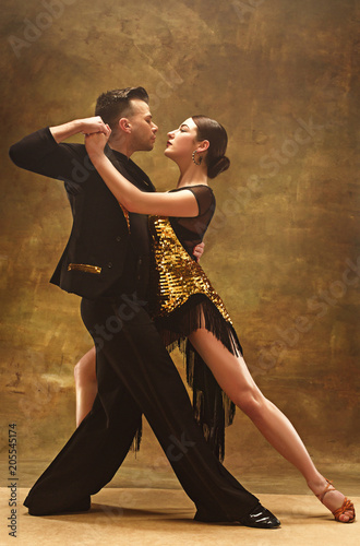 Photo Dance ballroom couple in gold dress dancing on studio background.