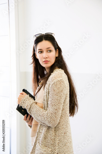 Poster young woman with beige knitted  cotton long cardigan