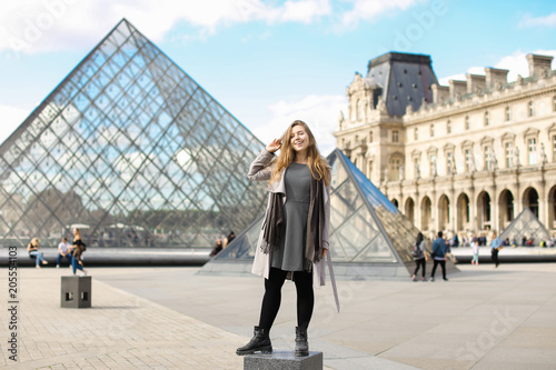 Fotografie, Obraz  Girl wearing grey coat and standing near Louvre and glass pyramid