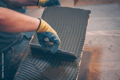 Photo  The working tiler applies glue on the tile with a notched trowel before gluing,
