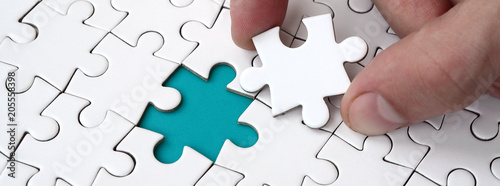 The human hand fills the last missing elements of the surface from the jigsaw puzzle. The concept of the completion of the initiated cases
