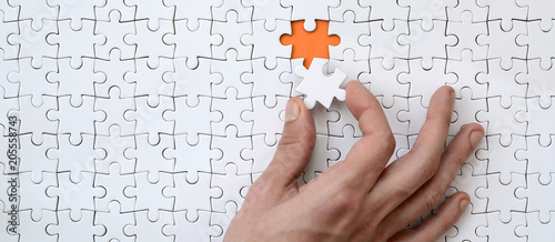 Fotografía  The texture of a white jigsaw puzzle in the assembled state with one missing ele