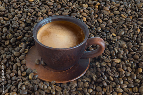 Foto op Canvas Cafe Cup of hot coffee against the background of fried coffee beans close up.