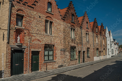 Brick facade of old houses with a blue sunny sky in an empty street of Bruges. With many canals and old buildings, this graceful town is a World Heritage Site of Unesco. Northwestern Belgium.