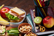 School or picnic lunch box with sandwich and various colorful vegetables and fruits on wooden background, close up.