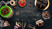 Assortment Of Desserts. On A Black Wooden Background. Top View. Copy Space.