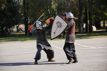 Two Men In Knight Costumes Are Fighting With Swords