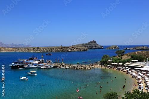 Fototapeta Turyści na plaży, statki i łodzie w zatoce morza Śrudziemnego. obraz