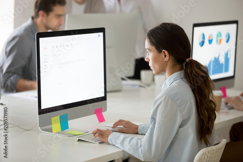 Serious young girl intern focused on writing email working on