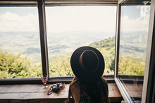Stylish Girl Traveler Ih Hat Sitting At Window In Cottage With View On Mountains And Sky. Happy Hipster Woman With Photo Camera Relaxing. Summer Vacation Concept. Travel And Wanderlust.