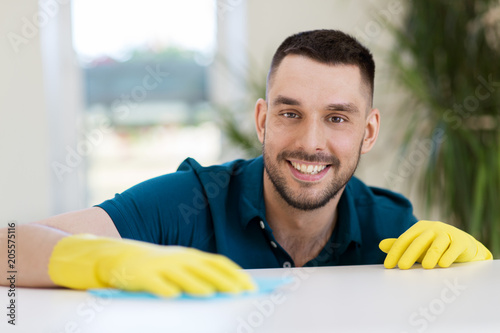 Fotografie, Obraz  household, cleaning and people concept - smiling man wiping table with cloth at