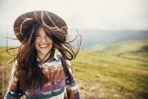 happy traveler hipster girl with windy hair smiling, standing on top of sunny mountains. space for text. stylish woman in hat. atmospheric moment. travel and wanderlust. space for text