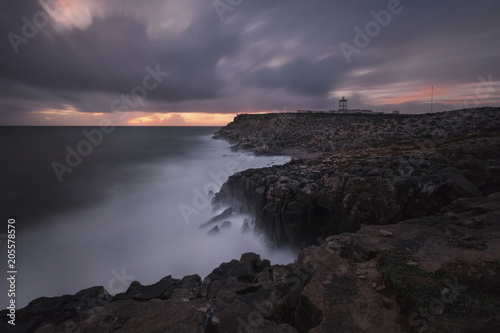 Distant view of lighthouse at coastline against cloudy sky during sunset