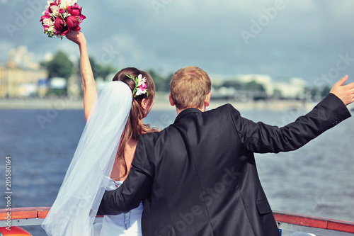 Photo Happy bride and groom hugging on a yacht at beautiful and wonderful sunny summer