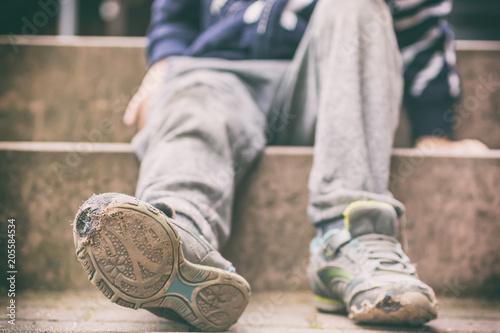 Alte kaputte Schuhe eines kleinen Jungen als Symbol für Kinderarmut Canvas Print