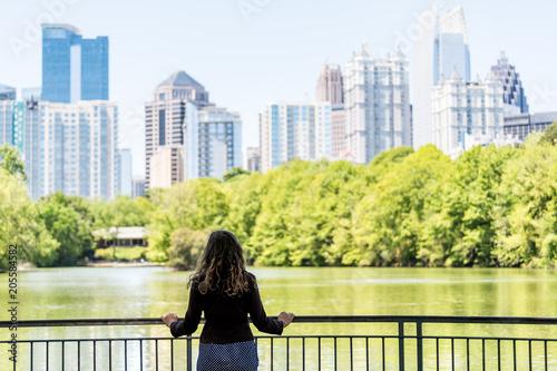 Plakat Młoda kobieta stoi w Piedmont Park w Atlancie, Georgia patrząc na malownicze wody i panoramę miasta miejskich drapaczy chmur w centrum, Lake Clara Meer