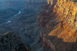 Surrounding the Colorado River, the Grand Canyon takes on an orange hue under the setting sun.