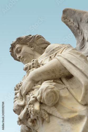 Photo  A low angel view of an angel statue appearing to look down protectively