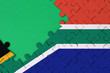 canvas print picture - South Africa flag  is depicted on a completed jigsaw puzzle with free green copy space on the left side