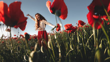 Young Beautiful Woman Walking And Dancing Through A Poppy Field