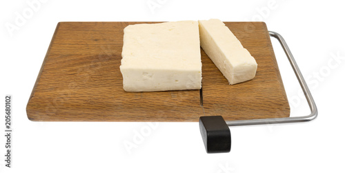 Chunks of feta cheese on a wood cheese slicer isolated on a white background.