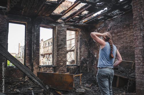 Sad man holds his head by hand and cry in burnt out house after disaster, conseq Canvas Print
