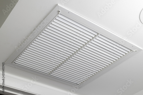Photo White Ceiling Air Filter Vent Grid One large white painted metal furnace air vent grill with many openings on a ceiling close-up