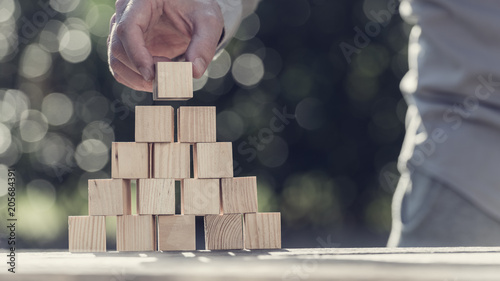Photo Retro toned image of man building a pyramid with blank wooden blocks outdoors