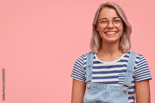 Canvastavla  Charming pleasant looking female in stylish denim dungaree and spectacles, liste