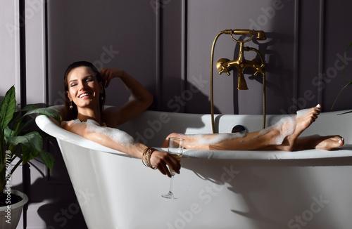 Young beautiful woman sitting in bathroom in expensive bathtub bath drinking cha Fototapete