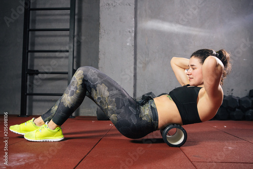 Fotografía  Beautiful young caucasian woman sportswoman uses a foam roller massager for relaxation, stretching muscles and back pain