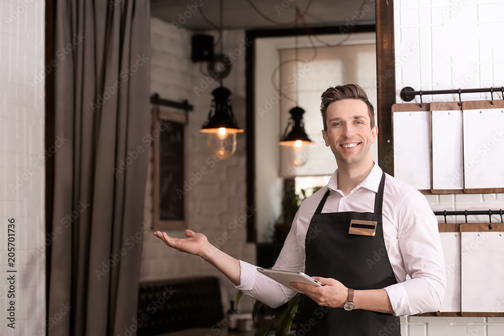Fototapeta Young waiter in apron with tablet computer at workplace