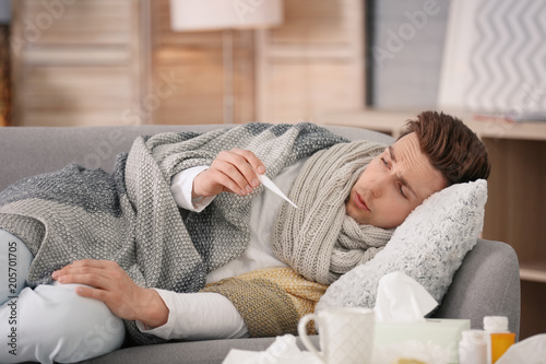 Fotografia  Sick young man with thermometer suffering from cold on sofa at home