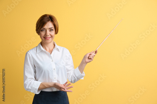 Portrait of female teacher with pointer on color background Fototapeta