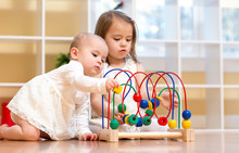 Toddler Sisters Playing With Toys Together Inside