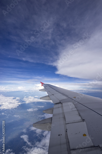 Foto Beautiful clouds with blue sky, through airplane window, aircraft wing on a side