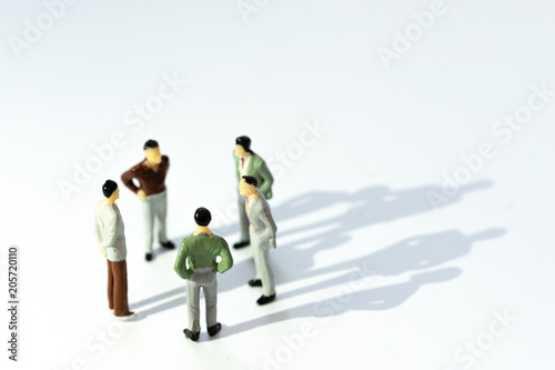 Fototapeta Business leadership, Teamwork power and confidence concept. Miniature people businessman small figure standing with talking on white background. With copy space for your text. obraz