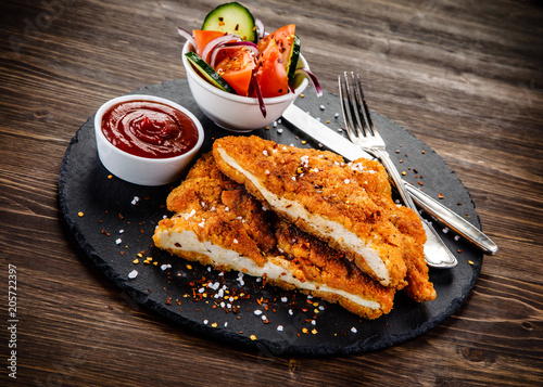 Fried pork chop with vegetables on wooden background