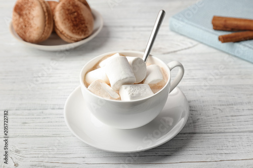 Tasty cocoa drink with marshmallows in cup on wooden table