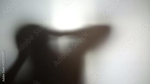 Fotografie, Obraz  Strange dark silhouette holding head in hands, hallucinations, desperate person