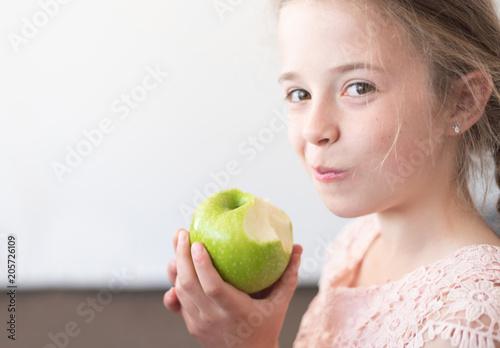 Fototapeta Mädchen isst einen Apfel obraz