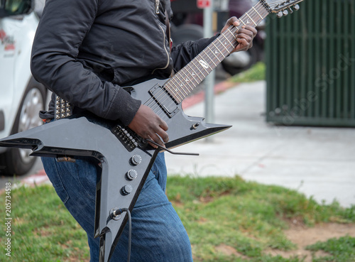 Fényképezés  Street musician strumming an electric guitar in an outdoor performance