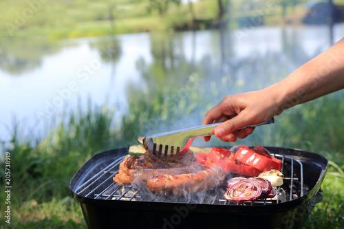 Kobieta griluje mięso, kiełbasę i warzywa na grilu turystycznym nad jezorem.
