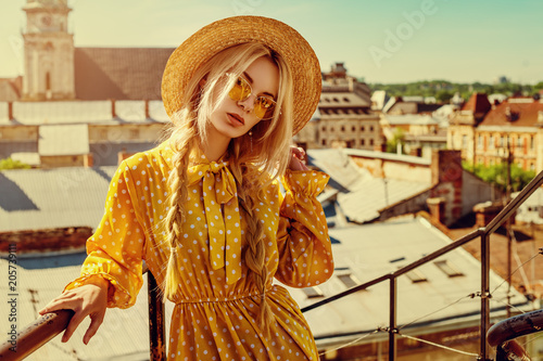 Photo Outdoor portrait of young beautiful girl wearing trendy yellow color sunglasses, straw boater hat, polka dot dress posing in street of european city