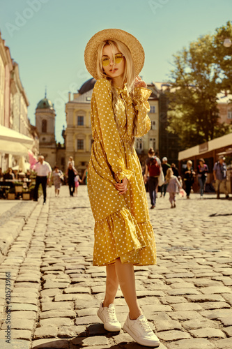 Outdoor full body portrait of young beautiful fashionable girl wearing trendy yellow color sunglasses, straw boater hat, polka dot dress posing in street of european city Canvas Print