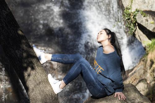 Mujer joven morena con pelo largo y liso sentada delante de una cascada Wallpaper Mural