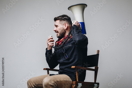Photographie Side view of young attractive movie director shouting on the megaphone while sitting on the chair isolated on grey background