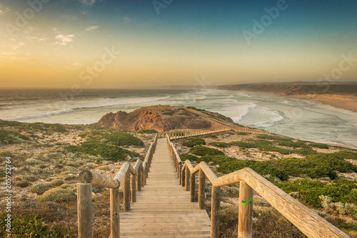 Canvas-taulu Wooden footbridge leading to the edge of a cliff above the ocean during sunset