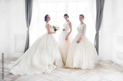 Fotografie, Obraz  Young woman with bouquets wearing wedding dresses